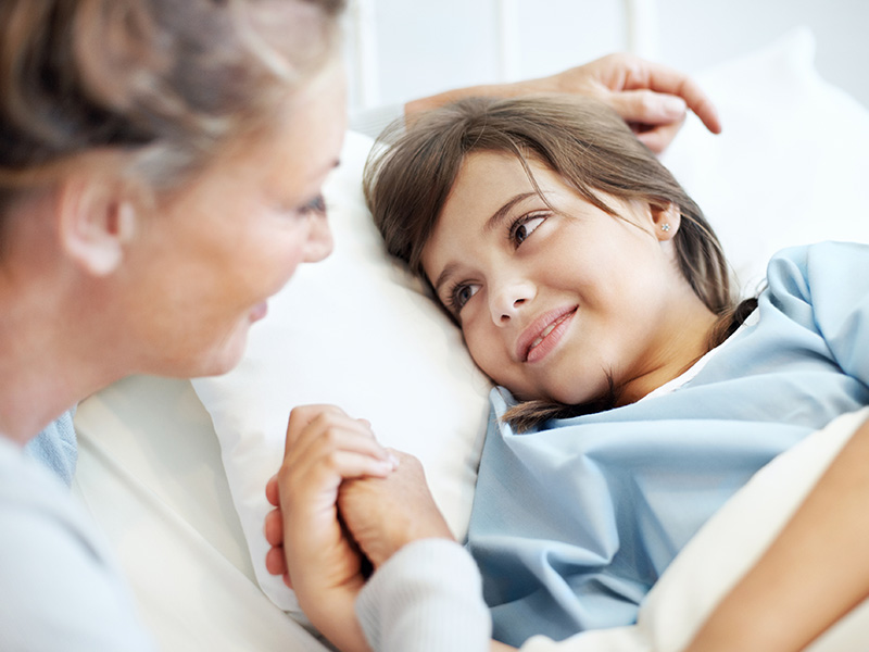 Mom smiling at her child who is in a hospital bed