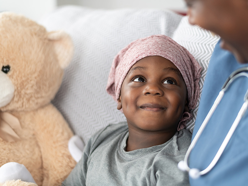 A young child lays on a hospital bed next to a teddy bear; the child smiles up at his physician who smiles back at him