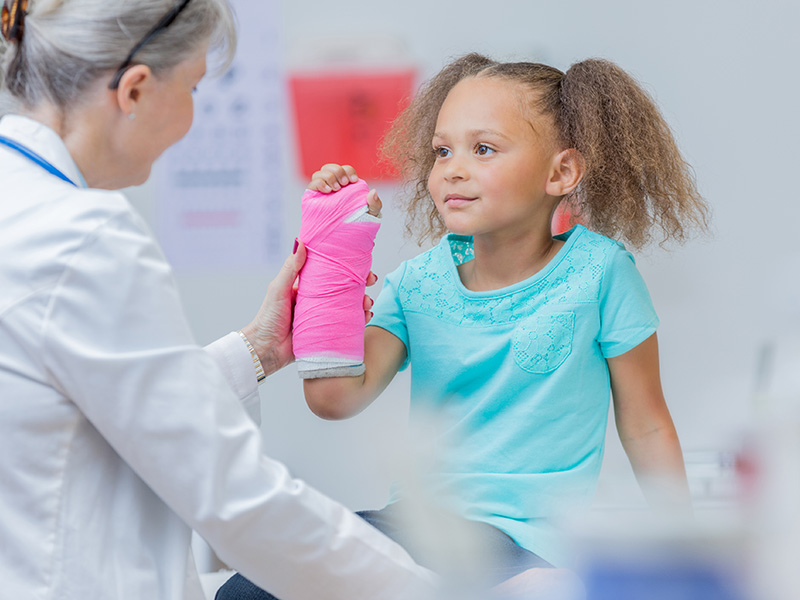 Pediatric orthopedic doctor examining a young girl who has a pink cast on her right arm