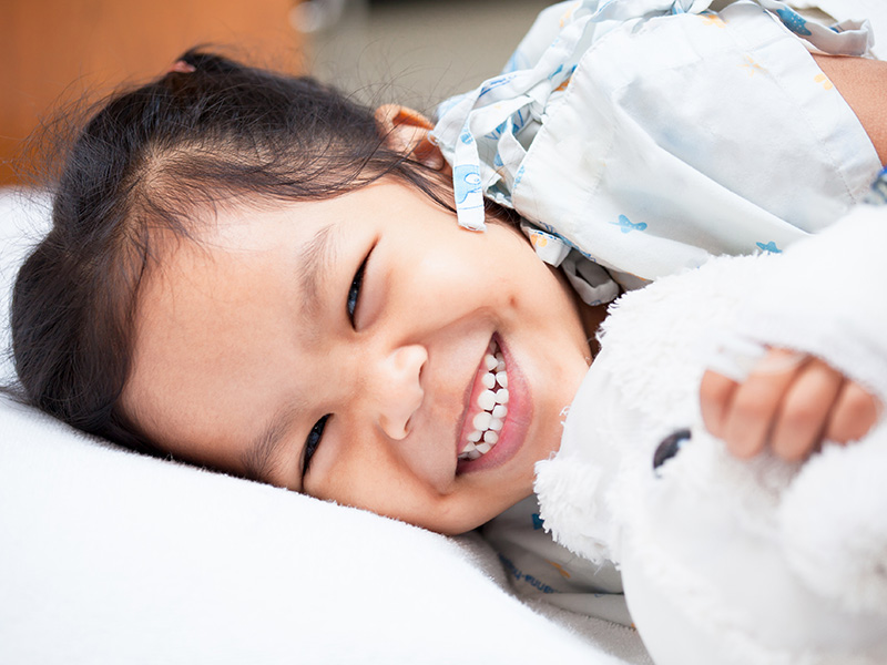Young child laying down on a hospital bed and smiling at the camera