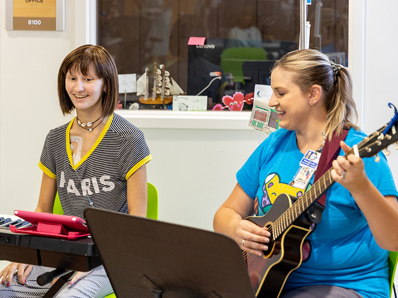 Young patient playing a piano next to a woman playing a guitar