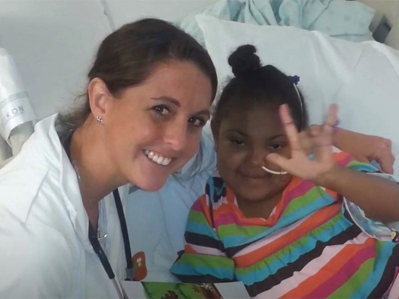 Smiling doctor next to a young patient who smiles and waves at the camera