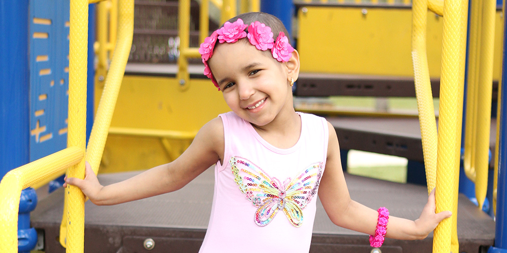 Salma in a playground smiling, she is wearing a pink ballet dress and a flower crown