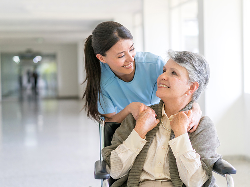 A nurse smiling and leaning over an older woman who is in a wheelchair and is smiling back