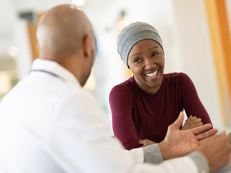 A woman wearing a head covering smiling as her doctor consults her