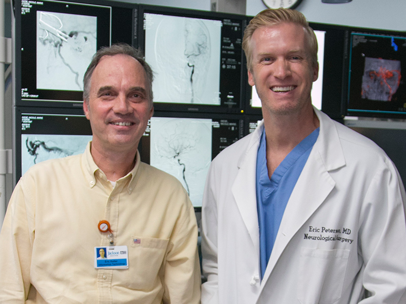 Eric Keller and Doctor Peterson standing next to each other and smiling, they are standing in front of x-rays