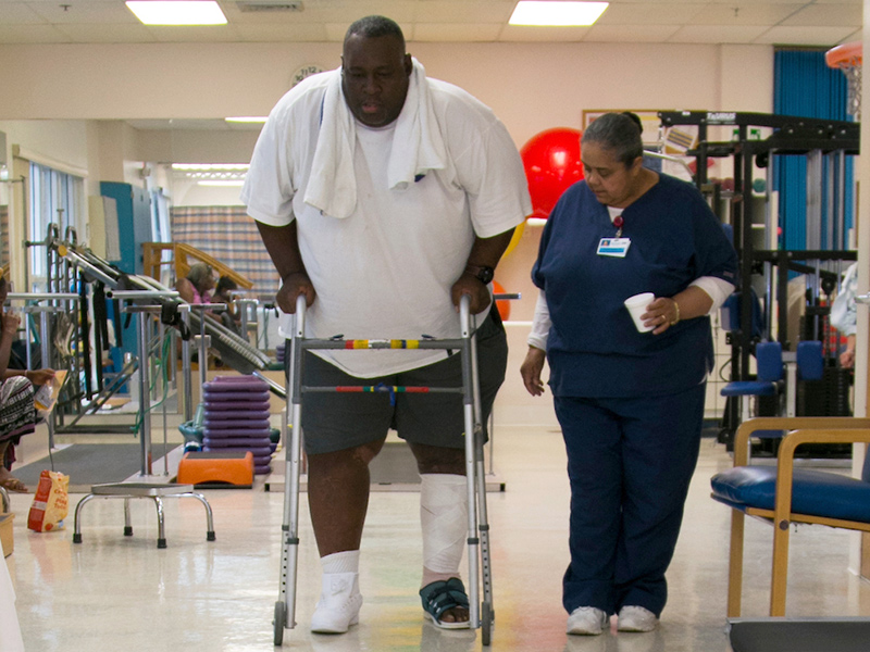 A physical therapist helping a patient walk with a walker, you can see his left leg is bandaged up