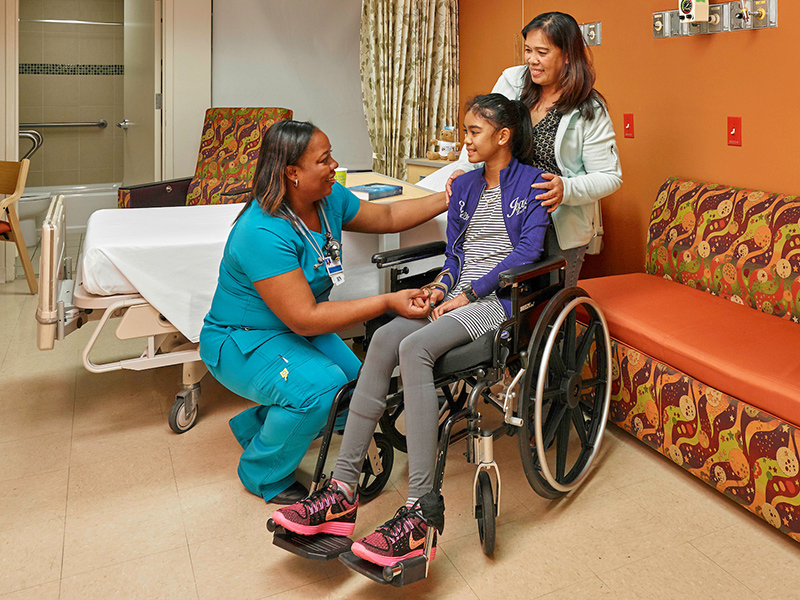 A healthcare worker smiling and holding the hand of a young girl who is in a wheelchair, her mom stands behind her