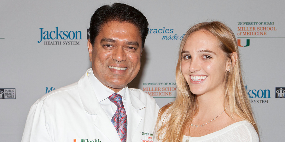 Isabel Vinueza standing next to doctor Yavagal, they are both smiling and standing in front of a step and repeat
