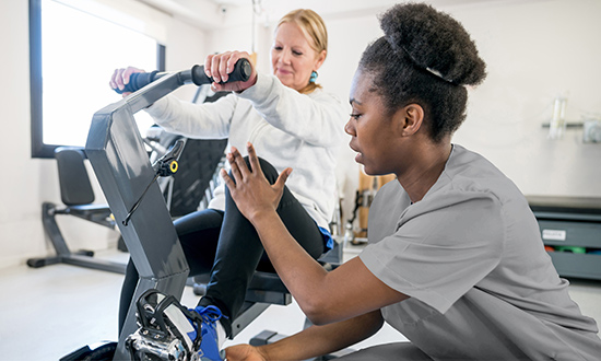 Physical therapist helping a women on a cycle machine