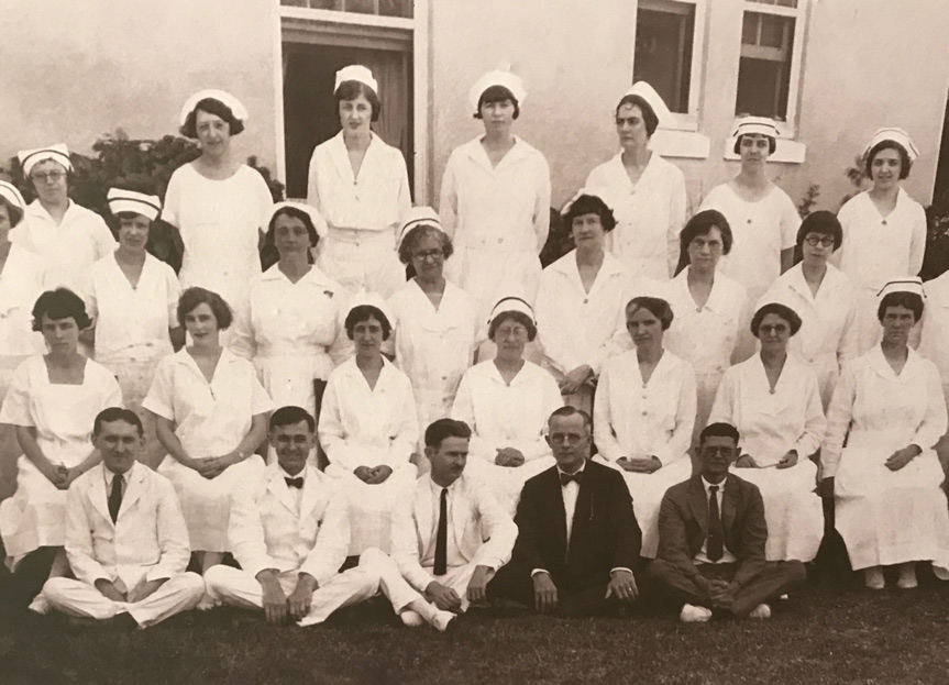 Black and white image of a group of nurses and physicians