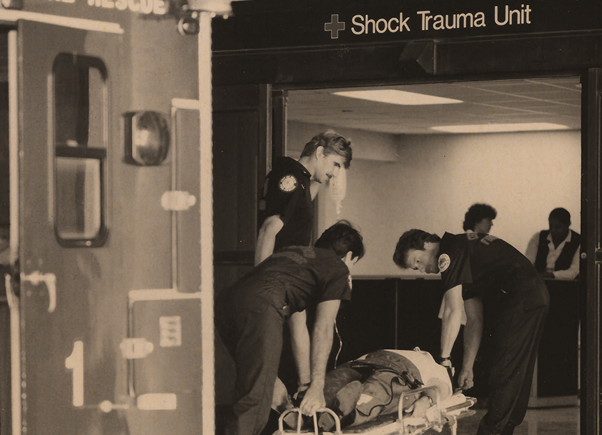 Black and white image of a person being brought into a shock trauma unit