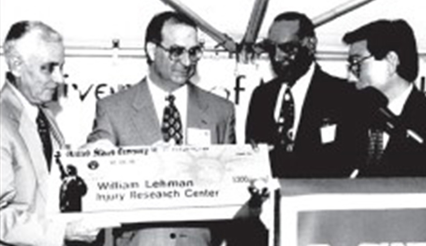 Black and white image of four men with a large check in front of a podium