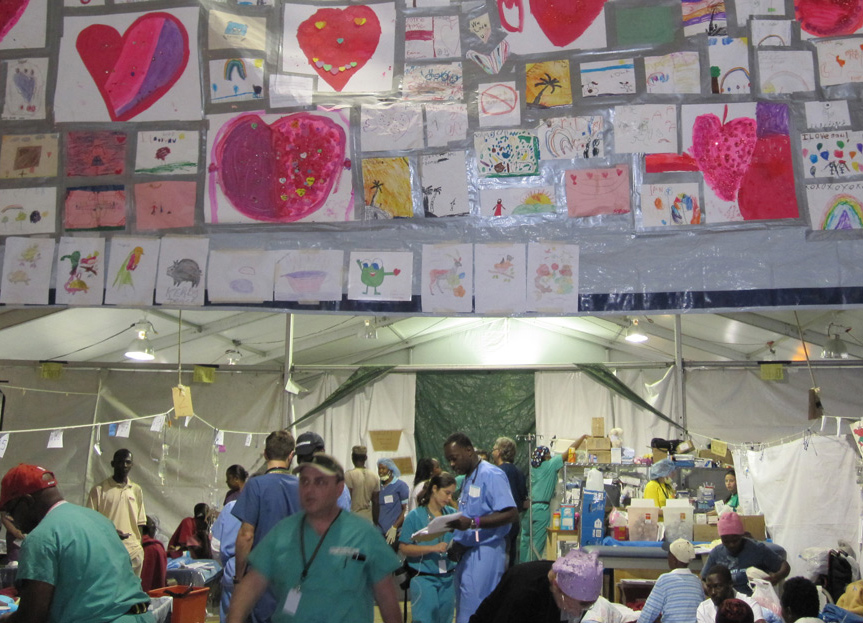 Physicians in a field hospital providing care to numerous people, you see hand drawings on the wall