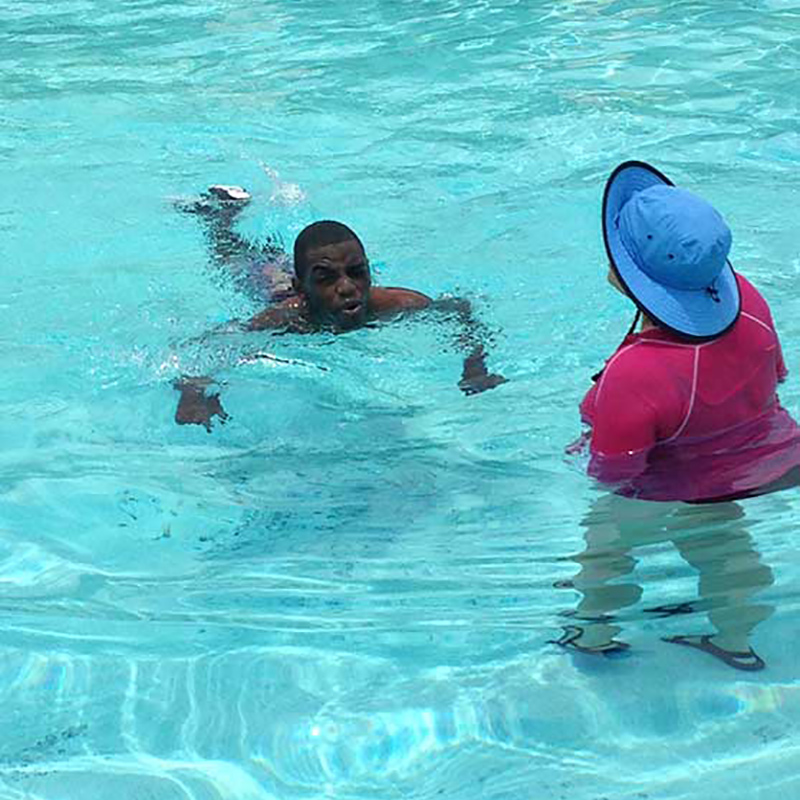 Aaron Willis swimming in a pool next to another person