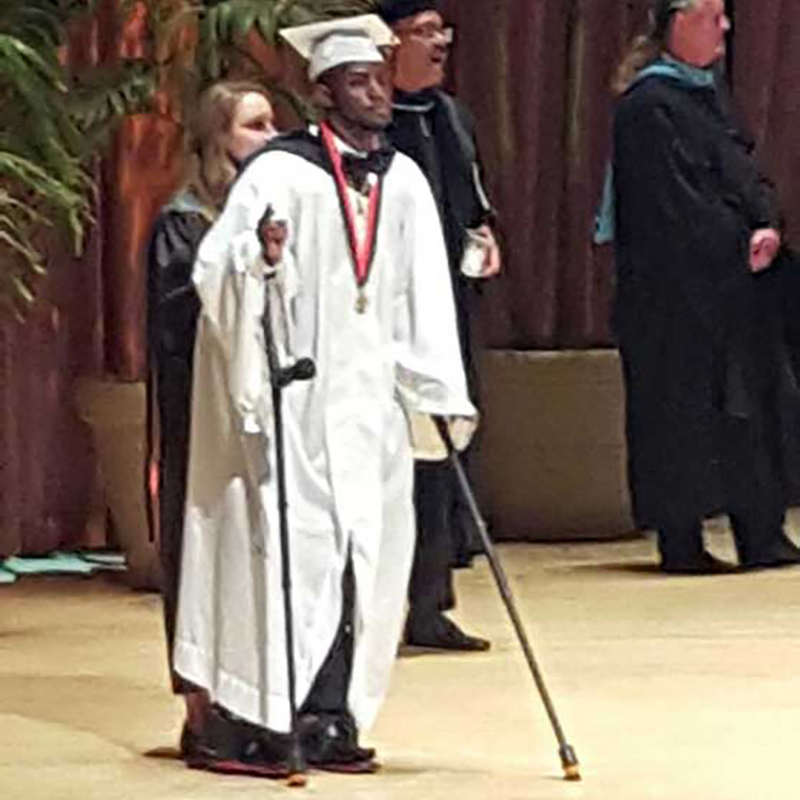 Aaron Willis with crutches as he receives his diploma and walks the stage