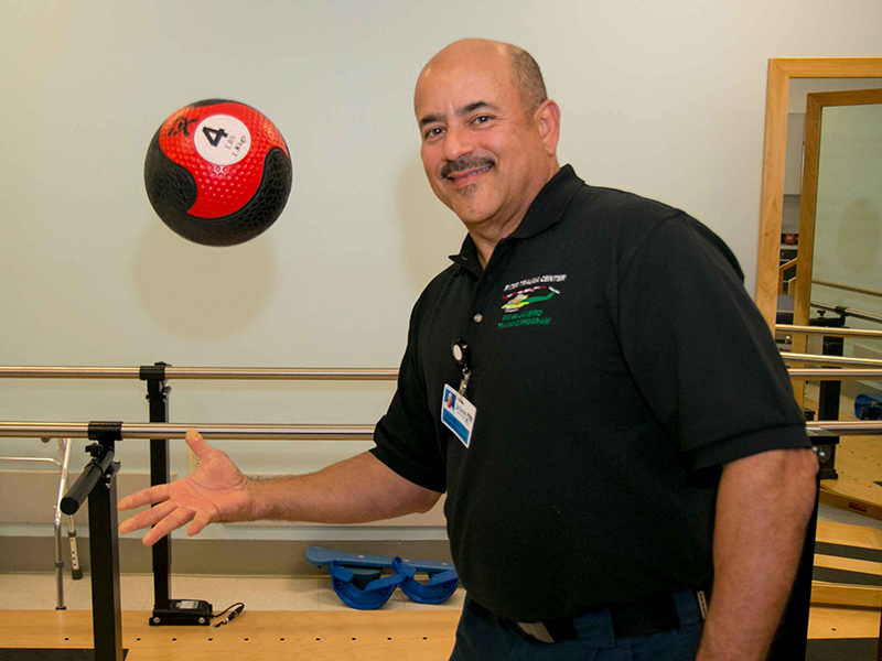 Angel throwing a four pound medicine ball up with his right hand, he is wearing a black shirt and is smiling at the camera