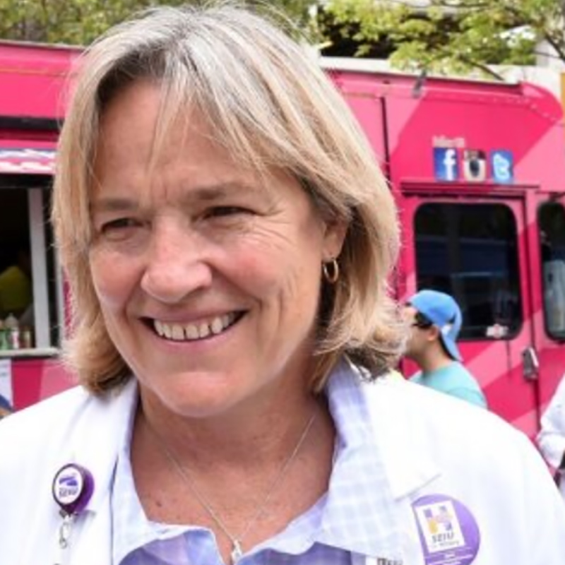 Martha smiling near a pink food truck, she has a white coat and a collared shirt on