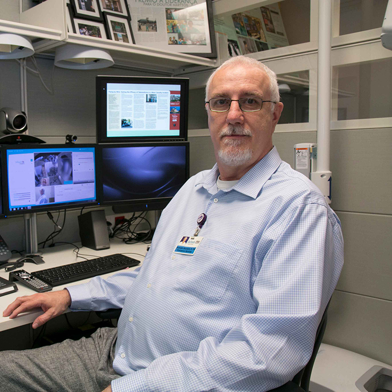 Bud sitting in front of three computer screens, he's wearing a collared button up shirt