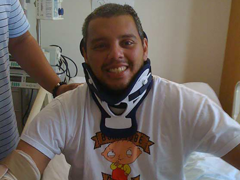 Carlos Castillo sitting up on a hospital brace, he is smiling and wearing a neck brace