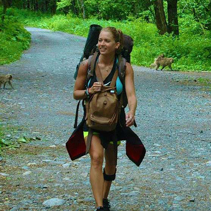 Danielle Press hiking outdoors, you can see two monkeys behind her