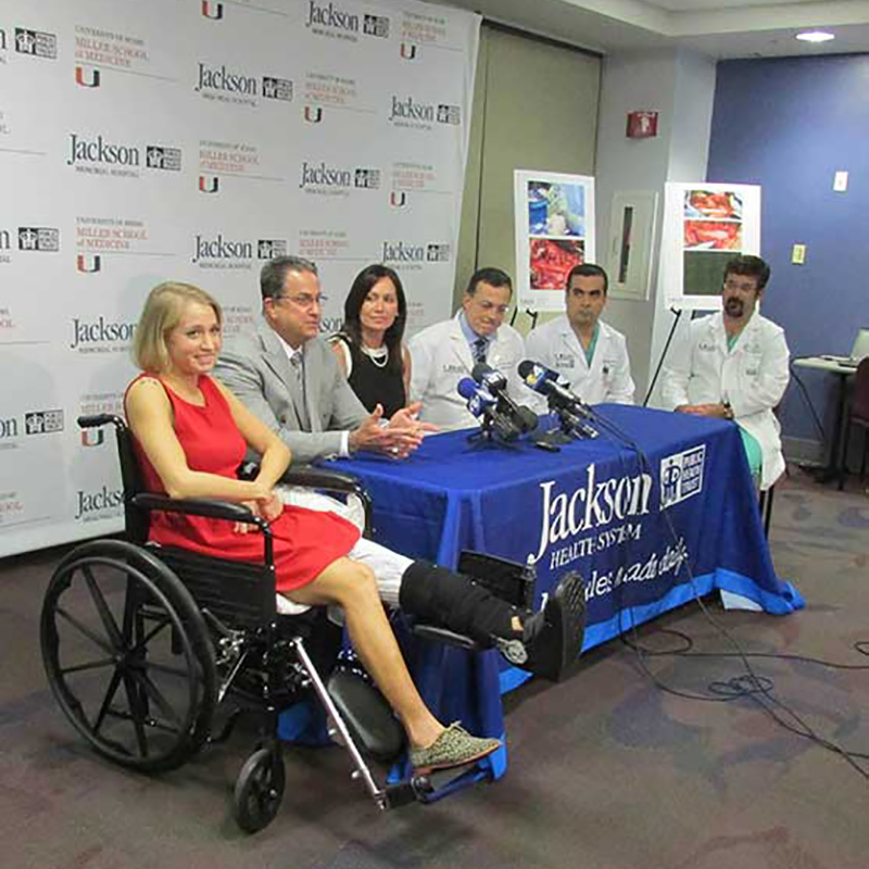 Danielle Press at a press conference, she is sitting on a wheelchair, doctors and Jackson employees sit beside her