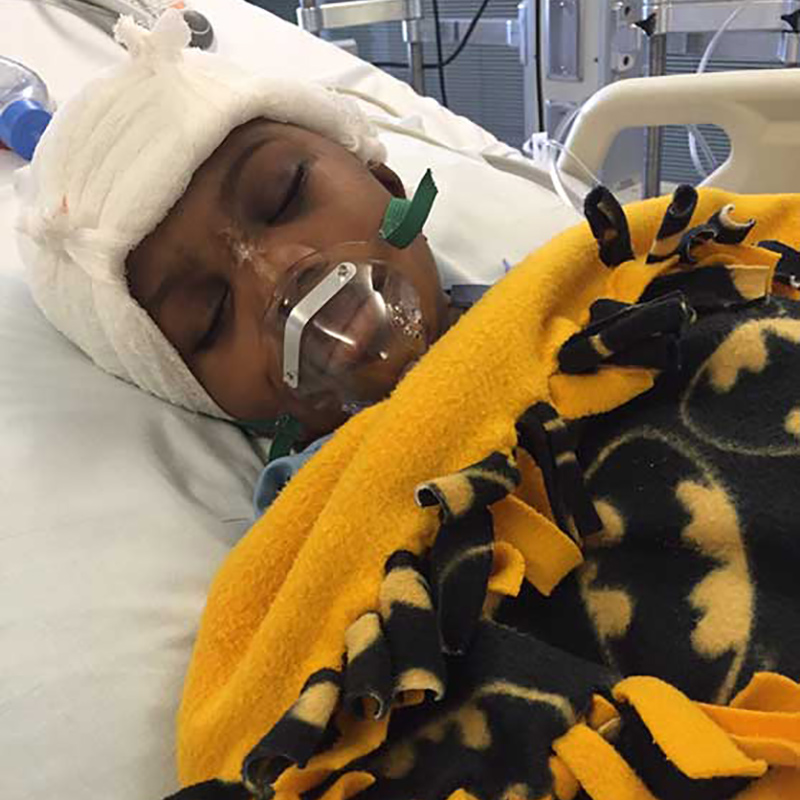 Darnal Mundy sleeping with a respirator on a hospital bed