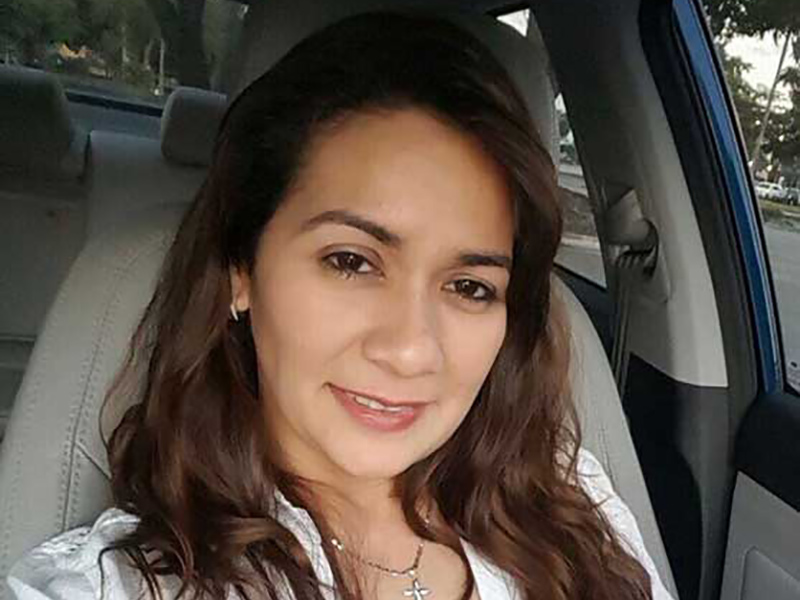 Evelin Matamoros smiling in a car, she's wearing a white shirt
