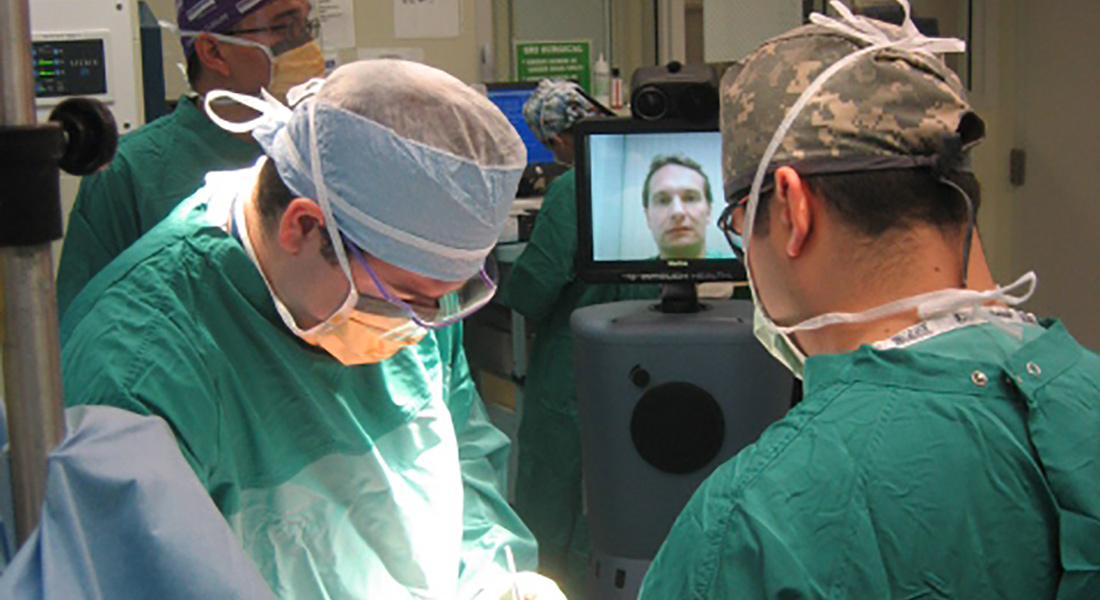 Two surgeons in surgery as a person communicates with them on a television screen