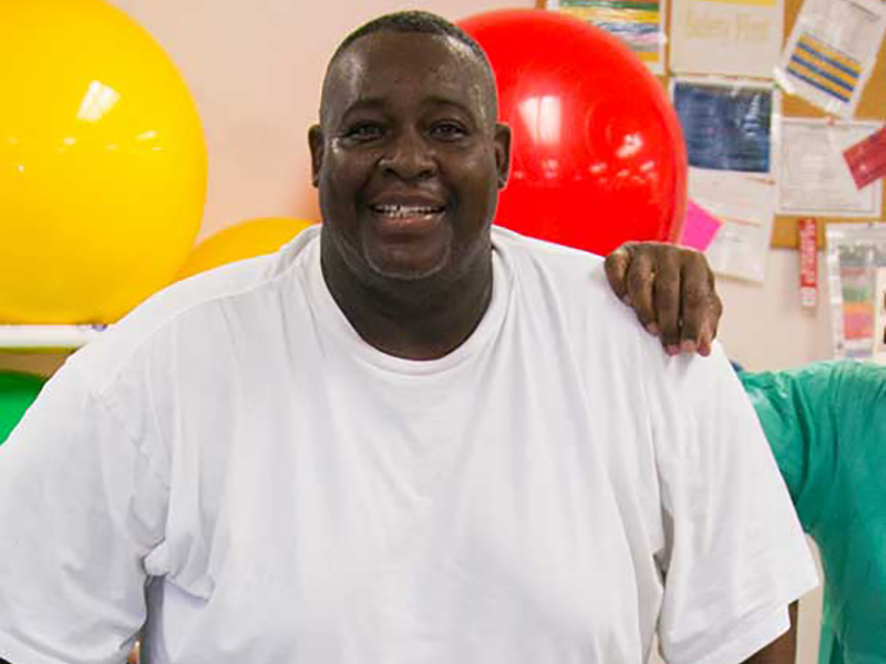 Closeup of Robert Billue during a therapy session, he's smiling and wearing a white shirt