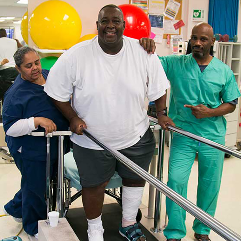 Robert Billue during a therapy session, two people are helping him walk