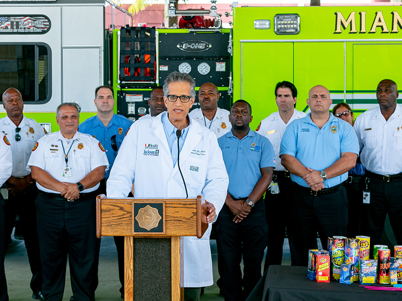 A physician in front of a podium, firefighters and EMT's stand behind him