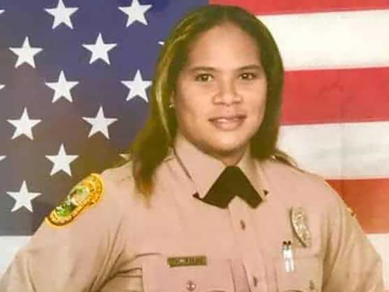 Jody Wright in her police uniform in front of an American flag