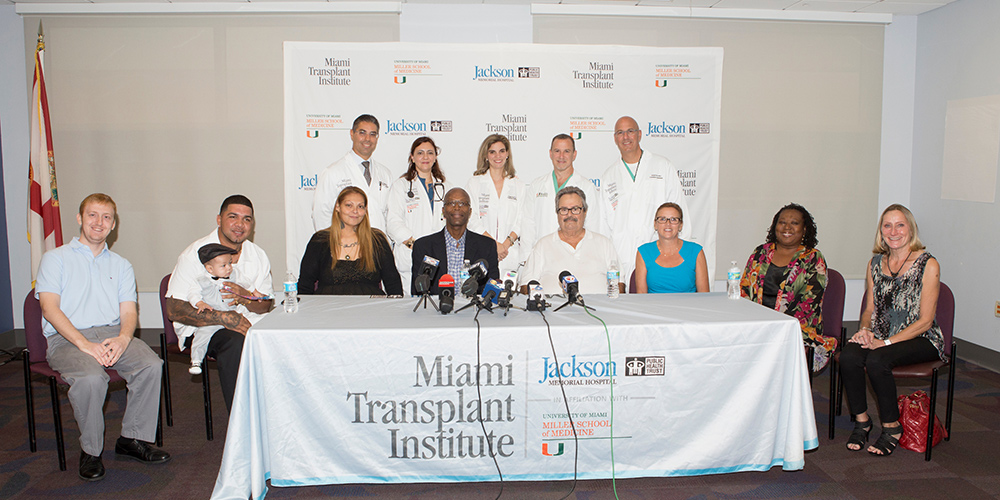 A group of people and physicians at a press conference, some are seated and some are standing in front of a step and repeat