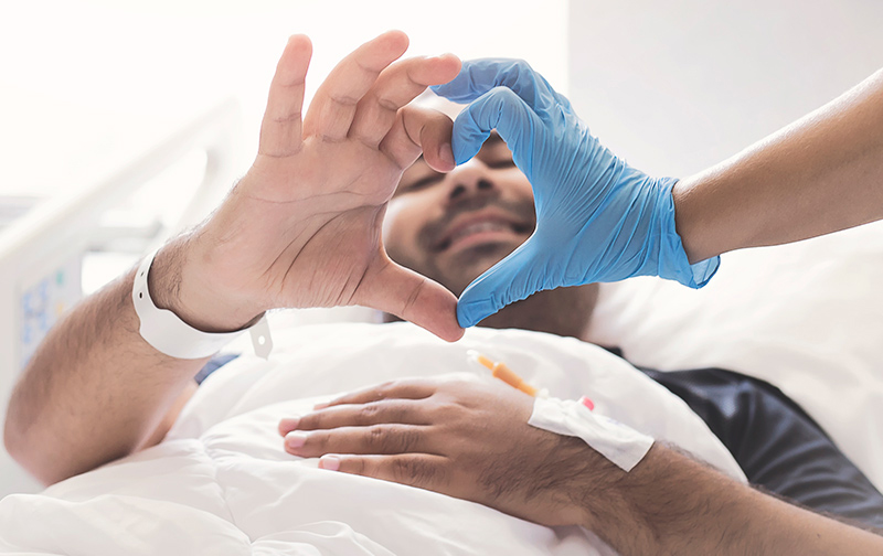 Closeup of a patients hand and a medical workers hand making a heart