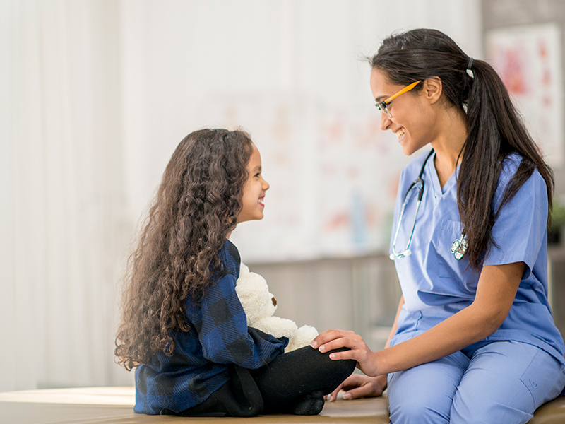 A healthcare worker sits across a young patient, they are both smiling at each other