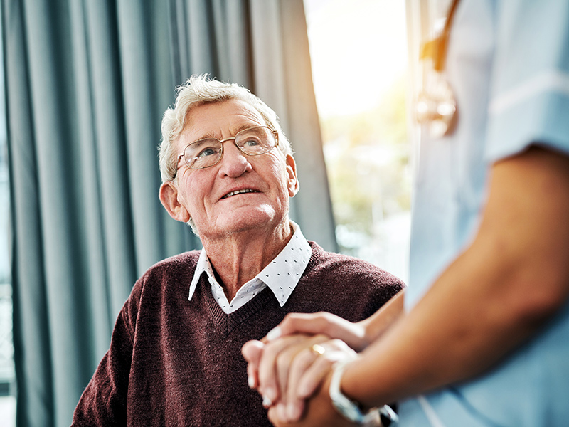 A nurse holding the hand of a senior patient who is sitting down