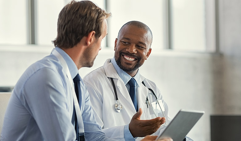 Two doctors sitting and looking at each other while one holds a tablet