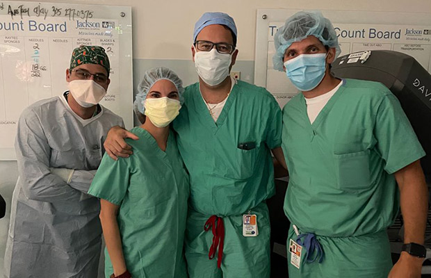 Four medical professionals standing next to each other, they are all wearing gowns and masks, they are looking at the camera