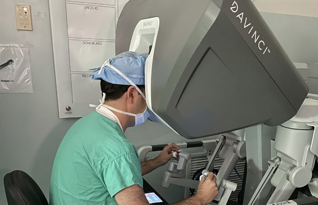A medical professional sitting, he is using a robotic machine