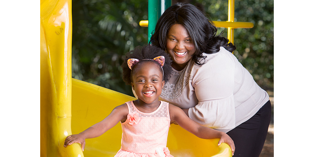Tanisha at the bottom of a slide with her mom standing behind her, they are both smiling at the camera