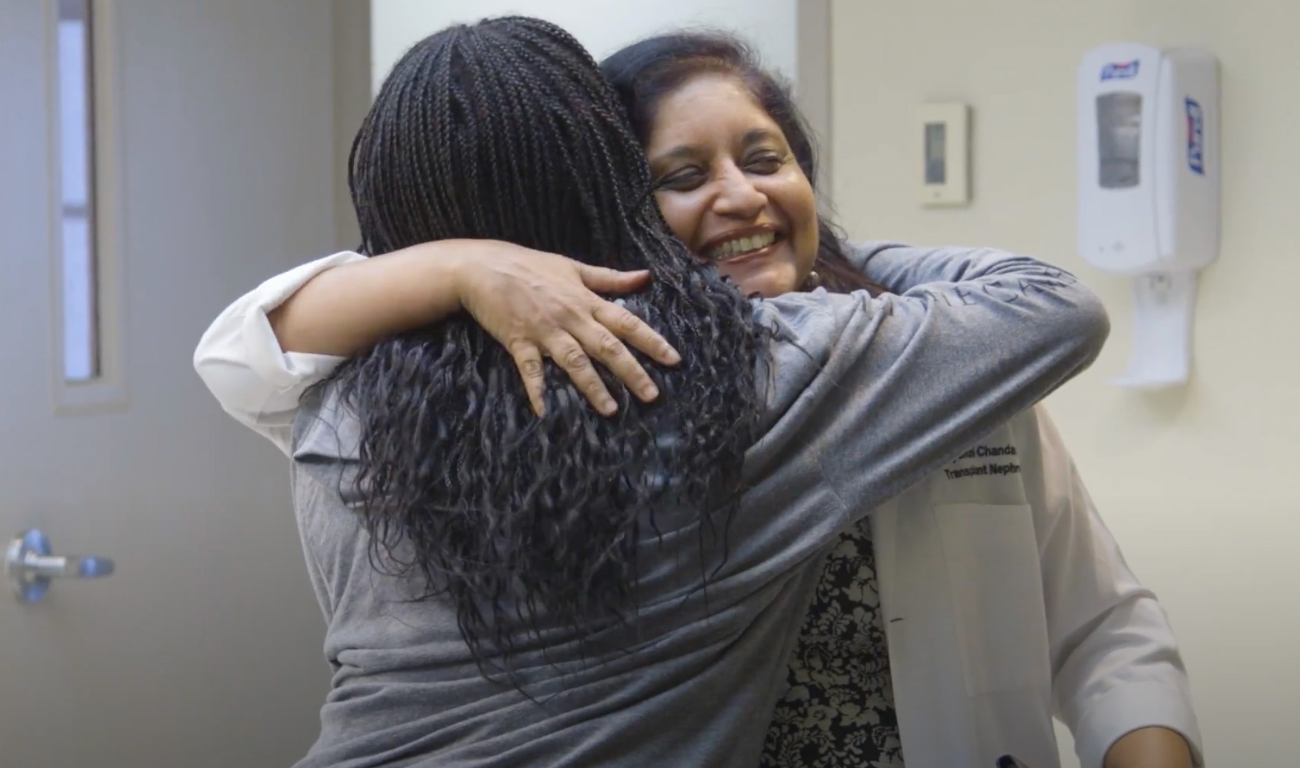 A transplant patient and doctor hug.