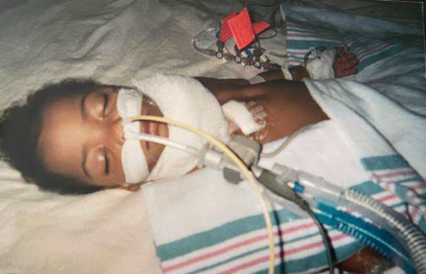 A baby in a hospital bed with tubes coming out of its nose