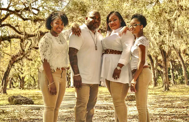 A family of four standing outside surrounded by trees, they all wear matching white and khaki outfits