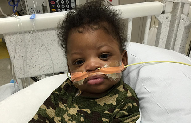 Baby with tubes coming out its nose, he is sitting on a hospital bed