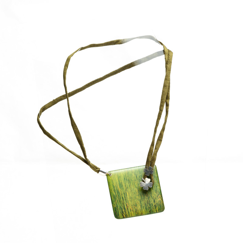 Necklace with square green charm containing a flower-shaped silver detail. Double fabric band with metallic claw. The Habitat series is inspired by green and nature, each accessory handicrafted with a printing on wood technique of details of macrophotographies.