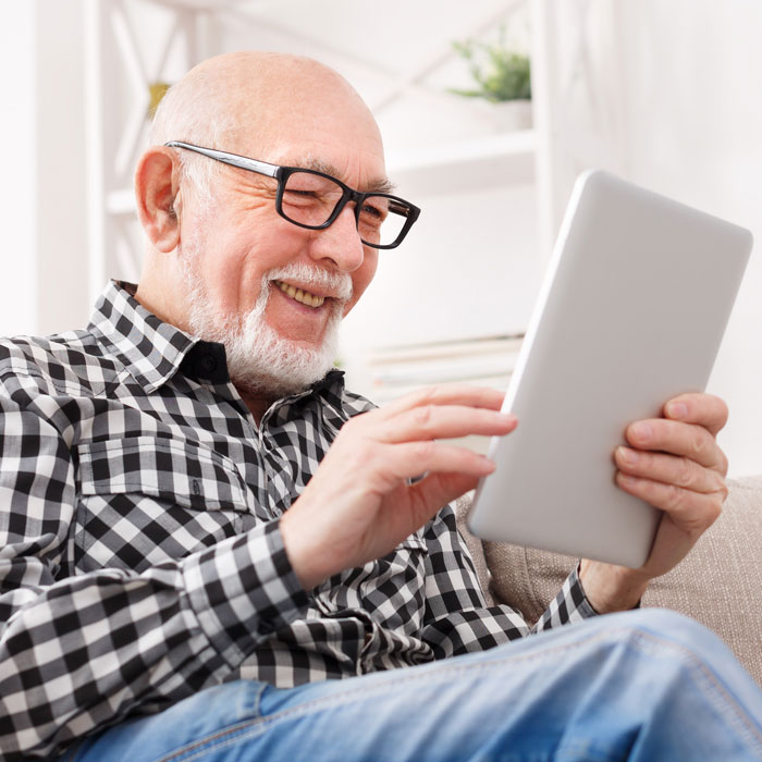 A senior man looking at a tablet