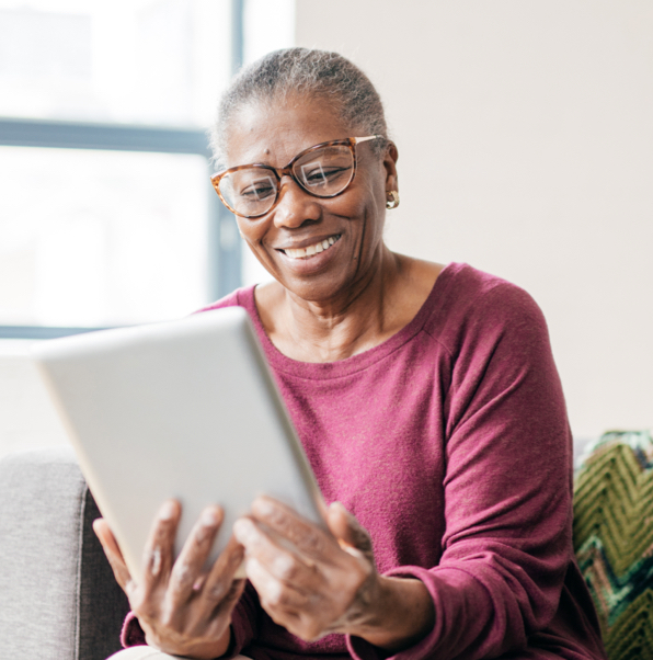 woman reading on tablet smiling