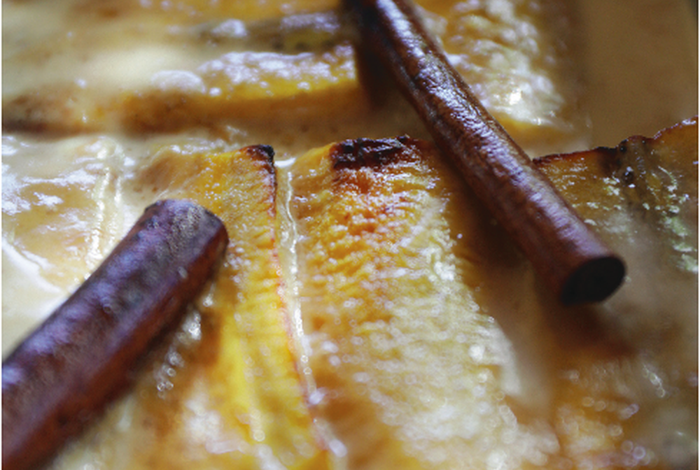 Close up of a layered plantain dish and a cinnamon stick.