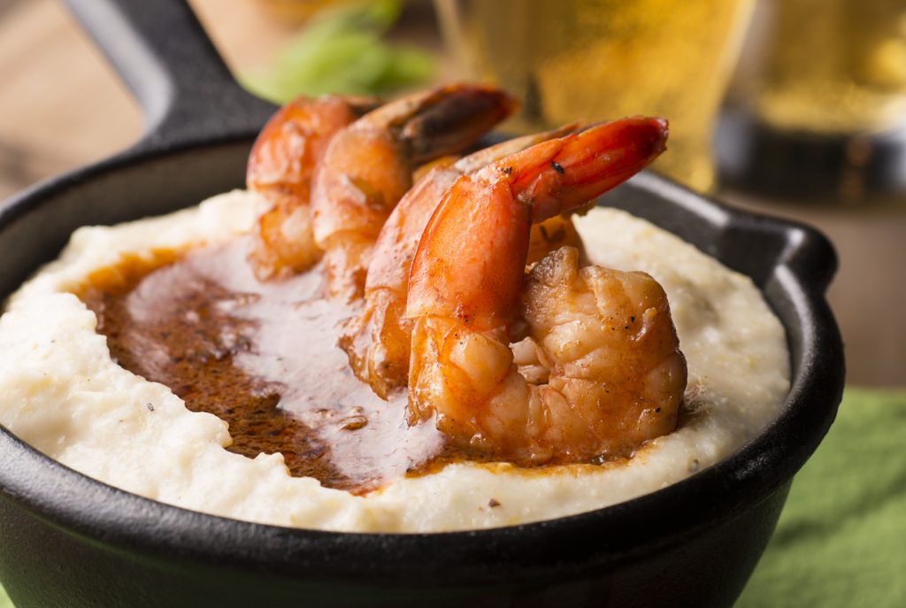 A close up on a cast iron pan full of shrimp and grits.